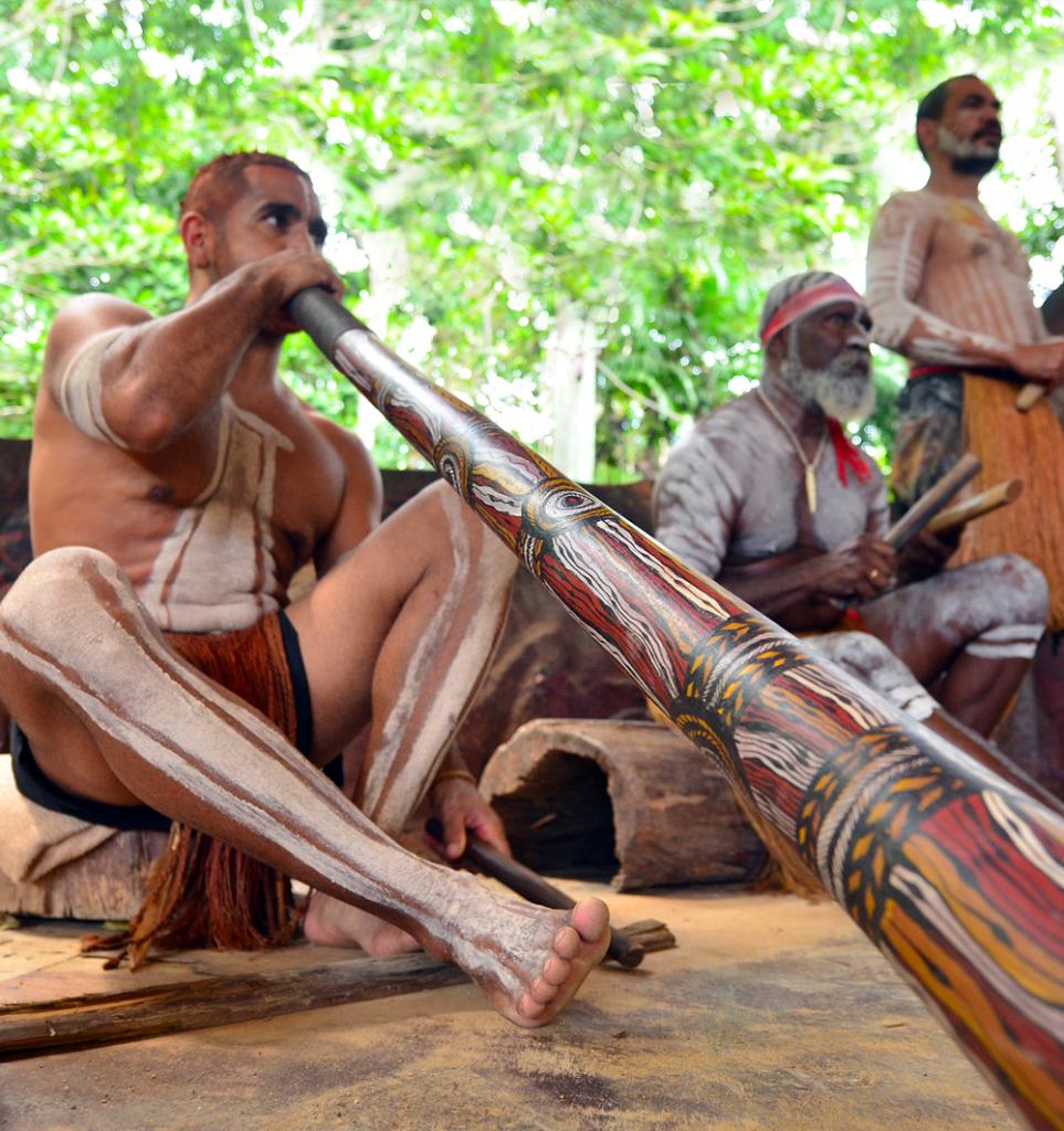 Indigenous aboriginals playing the didgeridoo representing diversity - indigenous business